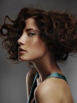 Стильная укладка локонами для коротких волос вьющегося типа идеально выглядит с боковым пробором и дополняется макияжем в золотисто-коричневых тонах