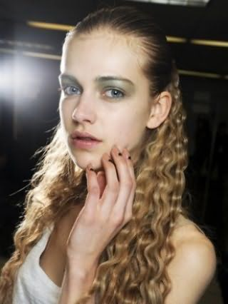 Укладка длинных волос в виде мелких локонов, зафиксированных на затылке, гармонично сочетается с макияжем глаз тенями в зеленой гамме