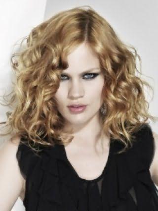 Вечерняя прическа на средние русые волосы в форме мелких локонов дополняется глубоким боковым пробором и гармонирует с макияжем в стиле смоки айс