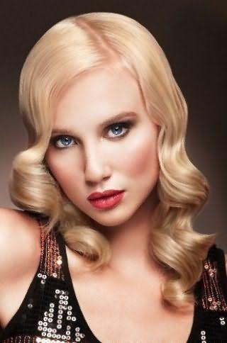Образ в стиле ретро для блондинки можно создать с помощью долговременной укладки на длинные волосы в форме крупных локонов от середины лица и дневного макияжа с акцентом на губы насыщенного красного цвета
