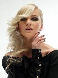 Очень нежная и романтичная прическа с распущенными волосами для блондинок с прядями средней длины. Удлиненная челка с концами, подкрученными во внешнюю сторону, укладывается на бок. Оставшиеся волосы, накрученные в локоны, также фиксируются на бок.