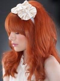 Отлично подчеркнут великолепие огненно-рыжего цвета распущенные волосы. Густая ровная челка фиксируется прямо. На остальных прядях создается начес, а концы укладываются в легкие локоны. Украсит прическу стильный ободок с искусственными цветами.