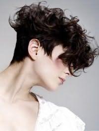 Дерзкая женская стрижка на короткие кудрявые волосы темно-каштанового оттенка, дополненная удлиненной челкой, и хаотично уложенными верхними прядками