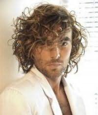 Удлиненный вариант мужской стрижки для кудрявых волос тонкого типа русого цвета идеально дополнен укладкой с хаотичными прядями на каждый день