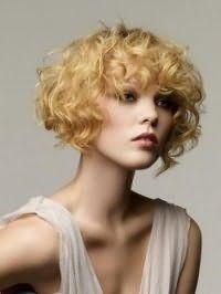 Стрижка на основе каре для блондинок с кудрявыми волосами средней длины позволит создавать элегантные образы, а густая челка гармонично дополнит лицо овальной формы