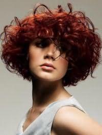 Объемная стрижка на средние кудрявые волосы подчеркнет красоту прямоугольного типа лица, а окрашивание в красный цвет сделает прическу яркой и ультрамодной