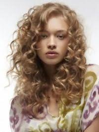 Женская стрижка, выполненная каскадом, на длинные кудрявые волосы идеально подойдет обладательницам светло-русых тонких локонов, а боковой пробор подчеркнет красоту овального лица