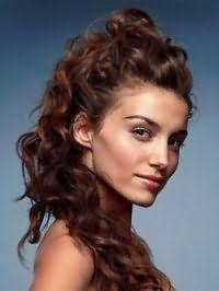 Длинные кудрявые волосы темно-каштанового оттенка можно уложить в высокую прическу с распущенными локонами, которые нежно смотрятся в варианте укладки на бок