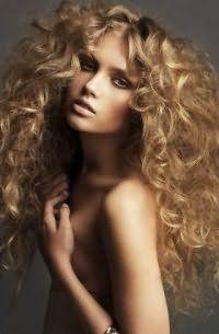 Объемная прическа для кудрявых распущенных волос светло-русого оттенка выполняется на длинных локонах с помощью тщательного начеса по всей длине прядей и дальнейшей укладки фиксирующими средствами
