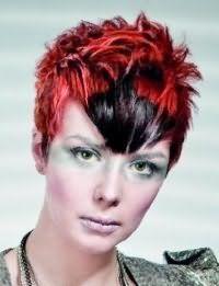 Короткая стрижка с рваными концами, уложенными в хаотичные пряди, отлично смотрится на волосах красного цвета с черным колорированием на челке и гармонирует с оригинальным вечерним макияжем