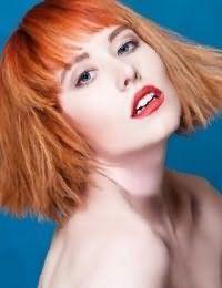 Стрижка каре на волосах пшеничного оттенка дополнит колорирование яркого рыжего цвета на челке, которое будет сочетаться с красной помадой и естественным макияжем глаз для светлого типа кожи