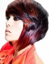 Креативная асимметричная стрижка каскад на прямых волосах черного цвета сочетается с колорированием бордового оттенка и гармонирует с макияжем глаз в стиле смоки айс и помадой натурального тона