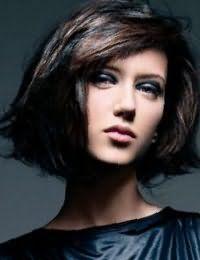 На волосах каштанового цвета великолепно смотрятся колорированные пряди изумрудного оттенка, которые украшают стрижку каре с дополнительным объемом и косой челкой
