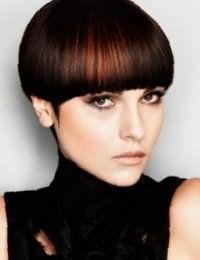 Короткая стрижка боб с дополнительным объемом на прямых волосах темно-каштанового цвета преображается благодаря колорированию рыжего оттенка и дополняется макияжем глаз черного тона, персиковыми румянами и бежевой помадой