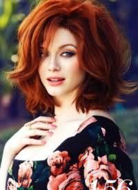 Объемная прическа в стиле ретро для густых волос медно-рыжего цвета идеально сочетается с вечерним макияжем с широкими стрелками и нежно-красной помадой