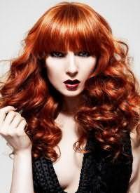 Укладка в виде мелких локонов для длинных густых волос огненно-рыжего оттенка гармонирует с прямой челкой и вечернем макияжем в стиле смоки айс