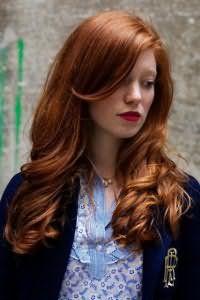 Длинные волосы натурального рыжего цвета, уложенные в крупные локоны, отлично дополняются удлиненной челкой на бок и макияжем с акцентом на губы