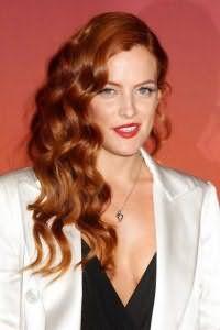 Вечерняя прическа в виде ретро локонов с боковым пробором для длинных густых волос огненно-рыжего цвета в сочетании с макияжем с широкими стрелками и ярко-красной помадой