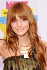 Длинные тонкие волосы светло-рыжего цвета, уложенные в виде легких локонов, дополняются прямой челкой и дневным макияжем в натуральных тонах
