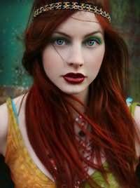 Греческая прическа с распущенными длинными волосами темно-рыжего цвета гармонирует с макияжем голубых глаз в зеленых тонах и помадой вишневого оттенка