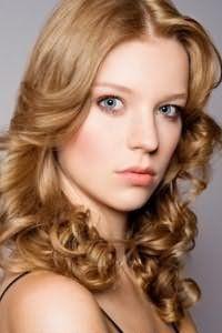 Стрижка каскад на средние волосы светло-карамельного оттенка, уложенная в виде мелких локонов в направлении от лица, гармонично выглядит с дневным макияжем в натуральных тонах