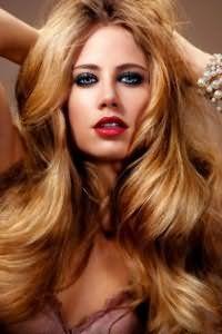 Девушки с длинными густыми волосами и теплым цветотипом могут смело окрасить локоны в золотисто-карамельный цвет, который хорошо дополняет вечерний макияж глаз смоки айс и губы ярко-красного оттенка