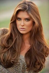 Повседневная укладка длинных густых волос карамельного цвета с боковым пробором и прикорневым объемом удачно сочетается с макияжем в золотисто-коричневой гамме