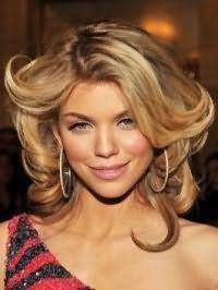 Каскадная стрижка на средние волосы Анны Линн, окрашенные в карамельный цвет и уложенные в направлении от лица, идеально сочетается с вечерним макияжем с черными стрелками, румянами и помадой светло-розового оттенка