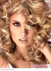 Длинные волосы кудрявого типа, окрашенные в светло-карамельный цвет, гармонируют с макияжем глаз в черно-коричневых тонах и помадой бледно-персикового оттенка