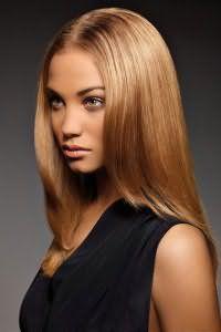 Выпрямленные волосы карамельного цвета в стрижке каскад гармонируют с легким дневным макияжем для обладательниц смуглой кожи