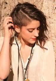 Креативная молодежная женская стрижка с выбритыми висками для средних волнистых локонов