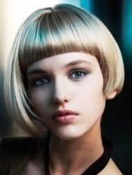 Асимметричный объемный боб с прямой круглой челкой в органичном сочетании с русым цветом волос, легким макияжем для зеленых глаз и помадой светло-бордового оттенка
