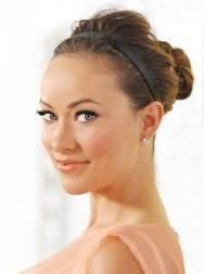 Длинные волосы светло-каштанового оттенка на прическе с тонким ободком черного цвета в виде высокого пучка гармонируют в сочетании с легким дневным макияжем