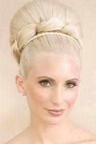 Модная прическа в ретро стиле с диадемой украсит платиновых блондинок. Волосы гладко зачесываются и собираются в объемную бабетту на макушке. Украшает её оригинальное плетение у основания. Прическа получается очень женственной и выглядит шикарно.