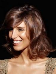 Великолепная прическа с распущенными волосами для обладательниц волос средней длины. Удлиненная челка фиксируется на бок, остальная масса волос обрамляет лицо, кончики подкручиваются во внешнюю сторону.