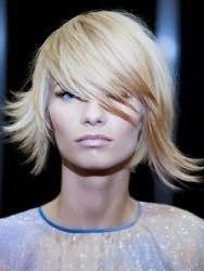 Асимметричная стрижка всегда выглядит оригинально, тем более в прическе на распущенные волосы. Из прически отделятся косая удлиненная челка, которая укладывается на бок. Остальные пряди фиксируются, завиваясь во внешнюю сторону.
