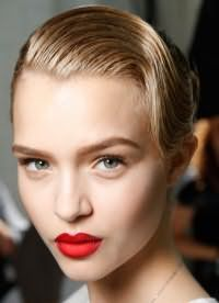 Роскошная прическа в ретро стиле. Волосам придается мокрый эффект, после чего они плавно зачесываются назад и на бок. Остальные пряди так же гладко укладываются. Прическа станет отличным решением для обладательниц светлых коротких или средних волос.