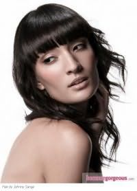 Очень элегантно стильно и женственно выглядит на черных прядях средней длины эффект мокрых волос. Пряди оформляются в легкие кудри, а густая ровная челка гладко укладывается. Волосы приобретают блеск и естественное сияние.