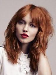 Вариант стрижки каскад для вытянутого лица и длинных волос медно-рыжего оттенка, который отлично дополняется челкой ниже бровей и глубоким прямым пробором