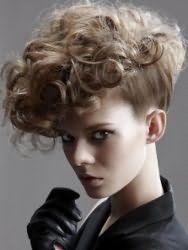 Креативная прическа на коротких кудрявых волосах достигается путем небольшого начеса в верхней части, приданию нижним прядкам гладкости и формированию искусственного ирокеза