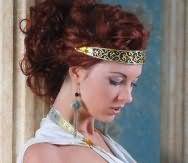 Вьющиеся длинные локоны оттенка красное дерево дополнят вечерний образ девушки с высокой греческой прической с широким металлическим ободком бронзового оттенка и легким макияжем