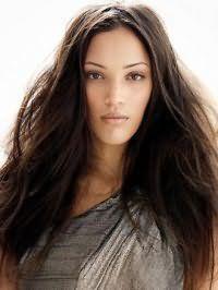 В данном роскошном образе длинные волосы каштанового цвета уложены в свободном беспорядке и разделены на зигзагообразный пробор. Особый шарм придает небрежность свойственная данной прическе.