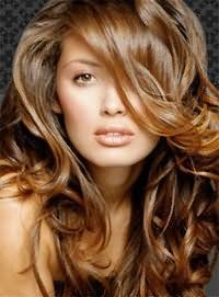Длинные волосы светло-каштанового цвета с укладкой в виде крупных локонов гармонично дополнят образ в сочетании с удлиненной челкой на бок, которая станет подходящей для теплого цветотипа внешности.