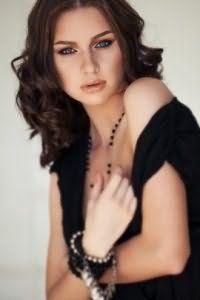 Стрижка каскад на длинные волосы, уложенные в крупные локоны с ровным пробором, отлично сочетается с темно-каштановым цветом волос и гармонирует с глазами голубого цвета.