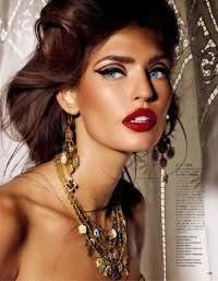 Очень изысканно, женственно и роскошно смотрится каштановый цвет волос в вечерней прическе. Длинные пряди со лба крепятся назад, а распущенные локоны не туго фиксируются ниже линии роста волос.
