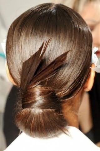 Длинные прямые волосы отлично выглядят в оригинальном низком пучке, перемотанным широкой прядью, концы которого выступают элементом украшения и надежно зафиксированы лаком