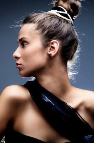 Пучок на макушке будет очаровательно выглядеть в сочетании с выбившимися волосами и заколкой в черно-белых цветах и дополнит легкий дневной макияж