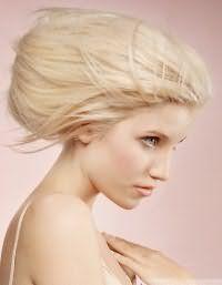 Весьма креативная прическа ракушка для блондинок. На волосах создается дополнительный объем, все пряди зачесываются назад и собираются в объемный вертикальный валик. Особый шарм прическе придадут выбившиеся прядки.