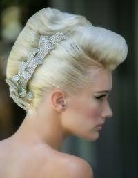 Очень красивая прическа ракушка, которая отлично смотрится на блондинках. Волосы на макушке начесываются и укладываются в объемный валик. Пряди с висков гладко зачесываются и вместе с остальными волосами собираются в классическую ракушку. Украсит прическу оригинальная заколка со стразами.