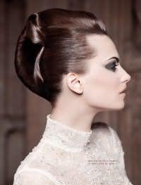 Изысканный образ с прической ракушка. На макушке волосы слегка начесываются, пряди с висков остаются гладкими и вместе с основной массой волос заворачиваются в вертикальный валик, концы которого укладываются изящной волной и фиксируются лаком.